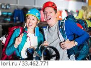 glad girl and guy select gear for hiking and camping in sports shop. Стоковое фото, фотограф Яков Филимонов / Фотобанк Лори