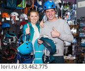 Купить «Young couple in sports shop choosing sports equipment», фото № 33462775, снято 25 октября 2017 г. (c) Яков Филимонов / Фотобанк Лори