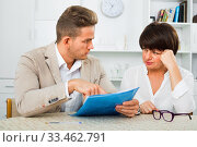 Купить «Man discusses correctness of paperwork with fellow worker», фото № 33462791, снято 15 июля 2020 г. (c) Яков Филимонов / Фотобанк Лори