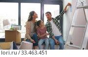 Купить «happy family with color palette moving to new home», видеоролик № 33463451, снято 22 марта 2020 г. (c) Syda Productions / Фотобанк Лори