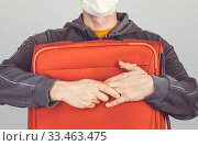 Frightened tourist man in a medical mask presses with red suitcase, the concept cant leave the country, flights canceled. Стоковое фото, фотограф katalinks / Фотобанк Лори