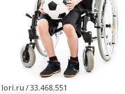Disabled child boy sitting on wheelchair holding soccer ball. Стоковое фото, фотограф Илья Андриянов / Фотобанк Лори