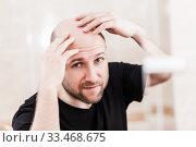 Bald man looking mirror at head baldness and hair loss. Стоковое фото, фотограф Илья Андриянов / Фотобанк Лори