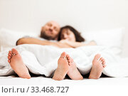 Loving caucasian couple in relationship lying and hugging on bed. Стоковое фото, фотограф Илья Андриянов / Фотобанк Лори