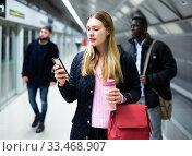Купить «Female passenger with phone waiting for subway train», фото № 33468907, снято 9 апреля 2020 г. (c) Яков Филимонов / Фотобанк Лори
