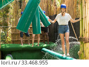 Купить «Young people try to walk the wet log in the theme park», фото № 33468955, снято 3 июля 2020 г. (c) Яков Филимонов / Фотобанк Лори
