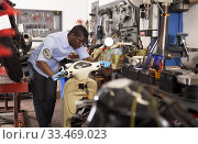 Confident man worker repairing motorcycle in workshop. Стоковое фото, фотограф Яков Филимонов / Фотобанк Лори