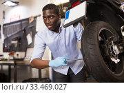 Afro american expert inspects the wheel of a motorcycle. Стоковое фото, фотограф Яков Филимонов / Фотобанк Лори