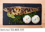 Купить «Deliciously baked whole trout with rice, served with lemon and greens», фото № 33469191, снято 5 августа 2020 г. (c) Яков Филимонов / Фотобанк Лори