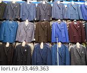 Ряды висящих новых мужских костюмов. Редакционное фото, фотограф Вячеслав Палес / Фотобанк Лори