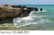 The clear water and surf waves near the rocky shore of the Ayia Thekla beach. Cyprus. Стоковое видео, видеограф Serg Zastavkin / Фотобанк Лори