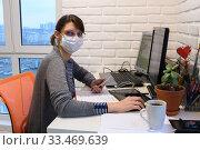 Купить «Заболевшая девушка в медицинской маске в самоизоляции работает удаленно, посмотрела в кадр», фото № 33469639, снято 31 марта 2020 г. (c) Иванов Алексей / Фотобанк Лори