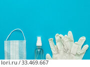 protective medical mask, gloves, alcohol disinfector on a blue background. Concept, fight, prevention, quarantine against coronavirus flu infection. View from above. Flat lay. Стоковое фото, фотограф Tetiana Chugunova / Фотобанк Лори