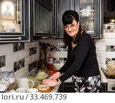 Купить «Счастливая женщина готовит еду на кухне», эксклюзивное фото № 33469739, снято 9 марта 2020 г. (c) Игорь Низов / Фотобанк Лори