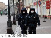 Полицейские в защитных масках патрулируют на улице Арбат в центре города Москвы во время эпидемии коронавируса COVID-19 в России. Редакционное фото, фотограф Николай Винокуров / Фотобанк Лори