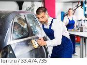 Купить «Mechanic grinding car body after puttying», фото № 33474735, снято 4 апреля 2018 г. (c) Яков Филимонов / Фотобанк Лори