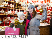 Купить «Woman and her daughter are preparing for Christmas and choosing balls on the tree», фото № 33474827, снято 19 декабря 2017 г. (c) Яков Филимонов / Фотобанк Лори