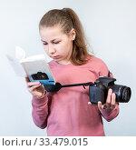 Preteen girl reading service manual book for her dlsr camera, beginner is learning photography, grey background. Стоковое фото, фотограф Кекяляйнен Андрей / Фотобанк Лори
