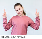 Portrait of a smiling young girl standing over grey background, holding fingers crossed for good luck. Стоковое фото, фотограф Кекяляйнен Андрей / Фотобанк Лори