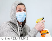 Scared man in hood with face mask cleaning with spray to protect him from Coronavirus. Covid-19 pandemic. Стоковое фото, фотограф Кекяляйнен Андрей / Фотобанк Лори