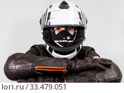 Motorcyclist folded arms wearing brown leather gloves, black and white crash helmet with facial mask, grey background. Стоковое фото, фотограф Кекяляйнен Андрей / Фотобанк Лори