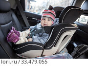 Child safety seat with smiling infant child is on back seat of car, kid eight month old. Стоковое фото, фотограф Кекяляйнен Андрей / Фотобанк Лори