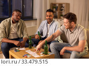 Купить «smiling male friends playing cards at home», фото № 33479515, снято 28 декабря 2019 г. (c) Syda Productions / Фотобанк Лори