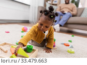 Купить «african baby girl playing with toy blocks at home», фото № 33479663, снято 29 сентября 2019 г. (c) Syda Productions / Фотобанк Лори
