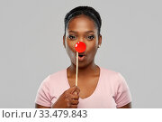 Купить «surprised african woman with red clown nose», фото № 33479843, снято 26 января 2020 г. (c) Syda Productions / Фотобанк Лори