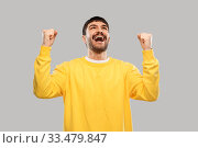 Купить «happy man in yellow sweatshirt celebrating victory», фото № 33479847, снято 22 февраля 2020 г. (c) Syda Productions / Фотобанк Лори