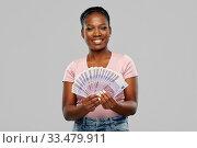 Купить «happy african american woman with euro money», фото № 33479911, снято 26 января 2020 г. (c) Syda Productions / Фотобанк Лори
