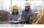 Купить «Two confident engineers discussing blueprint while standing at construction site», видеоролик № 33480479, снято 11 декабря 2019 г. (c) Яков Филимонов / Фотобанк Лори