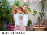 A little girl in a medical mask holds two more masks in her hands. Maximum protection during quarantine. Стоковое фото, фотограф Екатерина Кузнецова / Фотобанк Лори