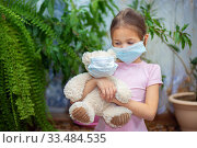 Купить «A girl in a medical mask sits at home during a Vieste epidemic with her teddy bear also in a mask», фото № 33484535, снято 1 апреля 2020 г. (c) Екатерина Кузнецова / Фотобанк Лори