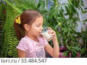 Купить «Girl drinks kefir from a transparent glass at home. Proper nutrition for the baby», фото № 33484547, снято 1 апреля 2020 г. (c) Екатерина Кузнецова / Фотобанк Лори