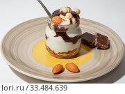 Купить «Sweet tasty milk curd creamy food in a glass jar of homemade breakfast. Cheesecake, English Trifle, Eton dessert, tiramisu, zuppa Inglese with nuts, almonds, cashews, hazelnuts, candied fruits and chocolate sauce», фото № 33484639, снято 14 декабря 2019 г. (c) Светлана Евграфова / Фотобанк Лори