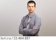 Купить «A belt portrait of an employee wearing a cage shirt and tie, crossed his hands on his chest. Isolated», фото № 33484887, снято 4 апреля 2020 г. (c) Владимир Арсентьев / Фотобанк Лори