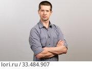 Купить «A worker in a cage shirt and tie crossed his hands on his chest. half-length portrait», фото № 33484907, снято 4 апреля 2020 г. (c) Владимир Арсентьев / Фотобанк Лори