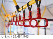 Grab handles in the passenger compartment of the bus on a blurred background. Стоковое фото, фотограф Евгений Харитонов / Фотобанк Лори