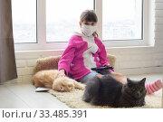 Заболевшая девочка на карантине сидит на полу с планшетом, рядом на ковре лежат коты. Стоковое фото, фотограф Иванов Алексей / Фотобанк Лори