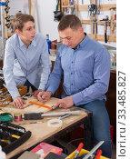 adult father teaching son сarpentry in the garage. Стоковое фото, фотограф Яков Филимонов / Фотобанк Лори