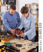 woodworker man and teenager with wood plank working in emerying machine at workshop. Стоковое фото, фотограф Яков Филимонов / Фотобанк Лори
