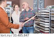 Купить «Young customers choosing kitchen facade», фото № 33485847, снято 4 апреля 2017 г. (c) Яков Филимонов / Фотобанк Лори