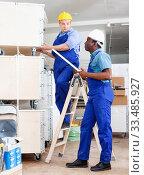 Купить «Two male builders working at indoors building site», фото № 33485927, снято 4 мая 2018 г. (c) Яков Филимонов / Фотобанк Лори