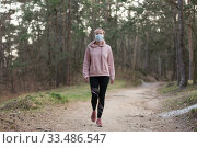 Купить «Corona virus, or Covid-19, is spreading all over the world. Portrait of caucasian sporty woman wearing a medical protection face mask while walking in the forest. Corona virus.», фото № 33486547, снято 28 марта 2020 г. (c) Matej Kastelic / Фотобанк Лори
