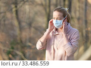 Купить «Portrait of caucasian sporty woman wearing medical protection face mask while walking in park, relaxing and listening to music. Corona virus, or Covid-19, is spreading all over the world», фото № 33486559, снято 28 марта 2020 г. (c) Matej Kastelic / Фотобанк Лори