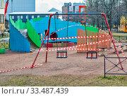 Закрытая детская площадка во дворе, во время карантина по коронавирусу (COVID-19). Сант-Петербург (2020 год). Редакционное фото, фотограф Сергей Афанасьев / Фотобанк Лори