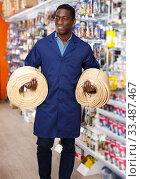 seller organizing assortment of items on shelves and racks. Стоковое фото, фотограф Яков Филимонов / Фотобанк Лори