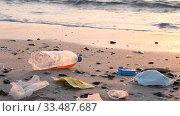 Купить «Close-up of face masks and plastic debris on the beath in surf zone. Coronavirus COVID-19 is contributing to pollution, as discarded used masks clutter polluting urban beaches along with plastic trash», видеоролик № 33487687, снято 5 апреля 2020 г. (c) Некрасов Андрей / Фотобанк Лори