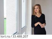 Красивая девушка смотрит в новой квартире в новостройке. Стоковое фото, фотограф Иванов Алексей / Фотобанк Лори